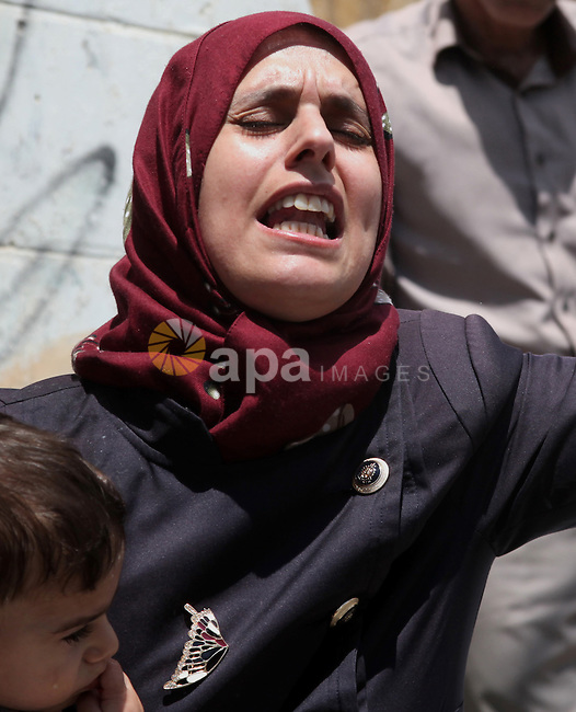 A relative of Palestinian Nader Driss, whom medics said died of a gunshot wound by Israeli troops during clashes at a protest against the Israeli offensive in Gaza, reacts during his funeral in the West Bank City of Hebron August 9, 2014. Violence picked up in the occupied West Bank, the Palestinian territory where President Mahmoud Abbas's Fatah movement holds sway, where Driss, a Palestinian man, 43, died of a gunshot wound to the chest from a confrontation with Israeli soldiers in the city of Hebron, medical officials said. Israeli troops shot and killed another Palestinian man, 20, on Friday at a protest near a Jewish settlement outside Ramallah, Israeli military officials said. Israel launched more than 20 aerial attacks in Gaza on Saturday, killing five Palestinians, and militants fired rockets at Israel as the conflict entered a second month, defying international efforts to negotiate an agreement for an extended ceasefire. Photo by Mamoun Wazwaz