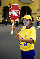Peru, Lima. Traffic Policewoman Stops Traffic to Allow Tourists to Cross.  Plaza de Armas.