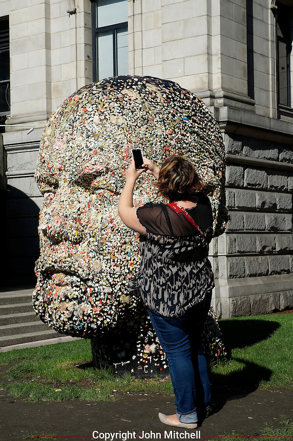 Woman using her cell phone to photograph Gumhead sculpture by Douglas Coupland outside the Vancouver Art Gallery, Vancouver, BC, Canada