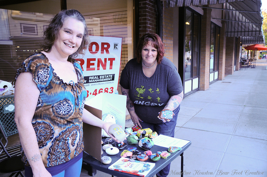Tawnya Fox and Kim Chesebro of Twin Cities Rocks share information about their group during Centralia, Washington's Third Thursday, a monthly event where downtown businesses stay open until 8 pm and art and music on the streets are encouraged.