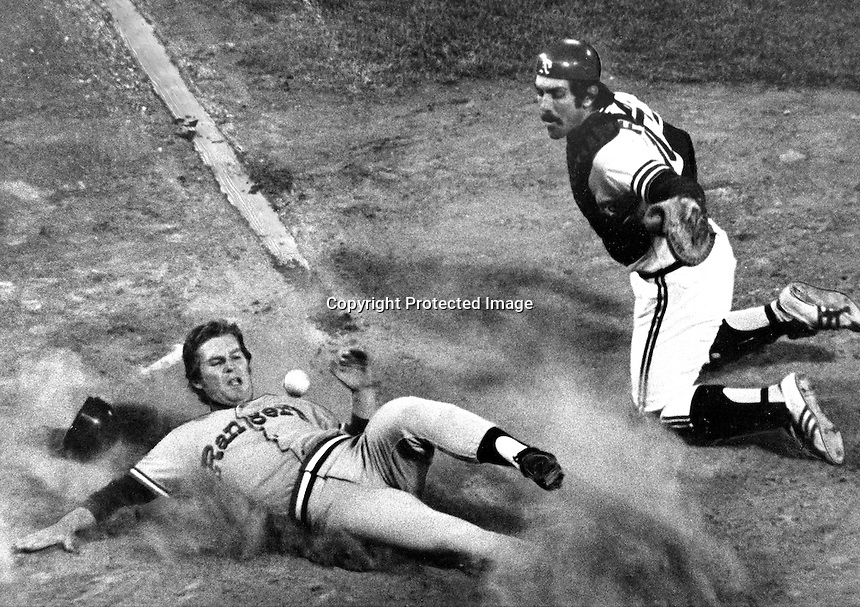 Texas Ranger Bill Sudakis slides safe into home ahead of the throw to Oakland Athletics catcher Ray Fosse.<br />