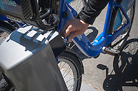 "Bicycle enthusiast insets his pass at a docking station in the Chelsea neighborhood of New York on Monday, May 27, 2013 on the first day of the city's bike-sharing program. 6000 bikes in over 300 stations have been placed so far for the roll out of the program. Cyclists purchased one-year passes for $95 which gives them unlimited 45 minute rides to get from point ""A"" to point ""B"". Daily and hourly passes will soon be available.  (© Richard B. Levine)"