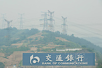 Daytime landscape view of Bank of Communications signage with power lines from the Chángjiāng Sānxiá Dàbà on the Cháng Jiāng in the Yiling District of Yichang in Hubei province.  © LAN