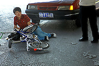 A cyclist is knocked down by a car in an accident in Beijing, China..