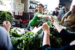 Huyen Phan helps customers at the Phan Farms stand in the Sunday Certified Farmers' Market in Sacramento, California.