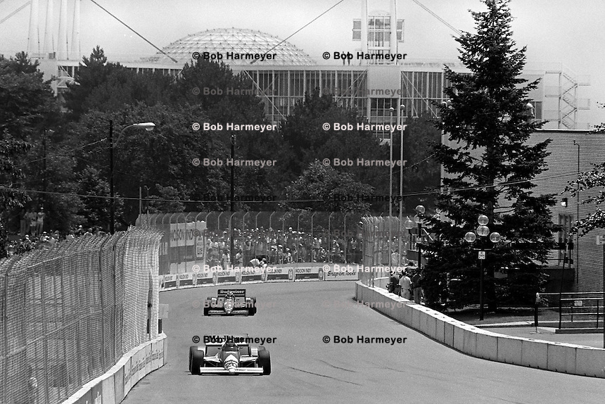 TORONTO, ON - JULY 20: Emerson Fittipaldi drives his Pat Patrick March 86C/Cosworth ahead of Bobby Rahal's March 86C/Cosworth during the Molson Indy Toronto CART Indy Car race on the temporary street circuit at Exhibition Place in Toronto, Ontario, Canada, on July 20, 1986.