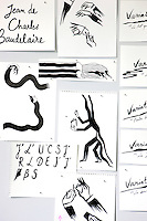 Black and white illustrations and work in progress are pinned to a wall of the studio