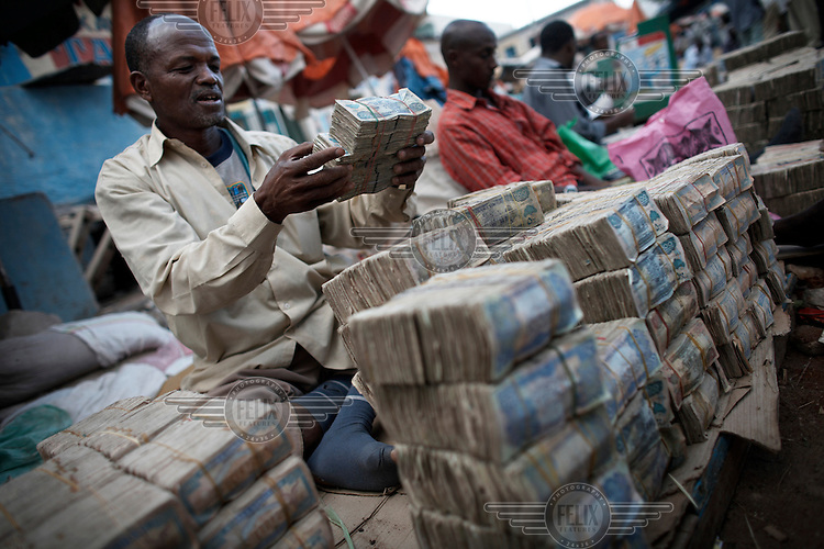 Money changers sit behind stacks of Somaliland Shilling notes in Hargeisa.