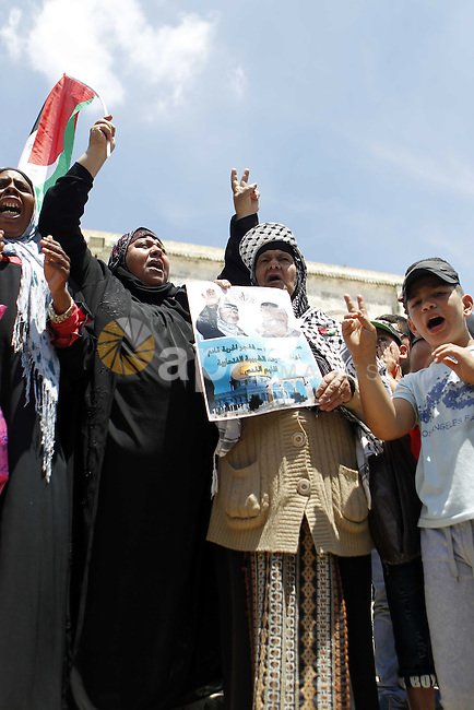 Protestors shout slogans during a demonstration in support of Palestinian Khader Adnan, a senior member of Islamic Jihad who is jailed in Israel without a trial, at the Al-Aqsa mosque in the old city of Jerusalem on June 5, 2015. Adnan has been on hunger strike for nearly 32 days to protest against his detention without trial. Photo by Saeb Awad