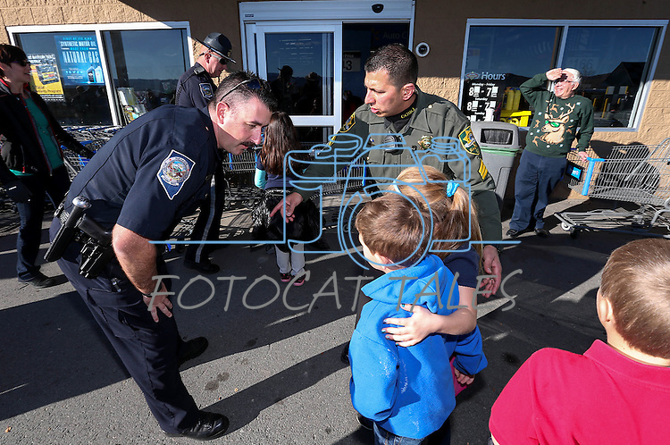 CCSO Sgt. Daniel Gonzales pairs volunteer hero shoppers with students at the 10th annual Holiday with a Hero event at Walmart in Carson City, Nev., on Wednesday, Dec. 17, 2014. The event provides Christams for 200 of Carson City's K-5th grade homeless students.<br /> Photo by Cathleen Allison