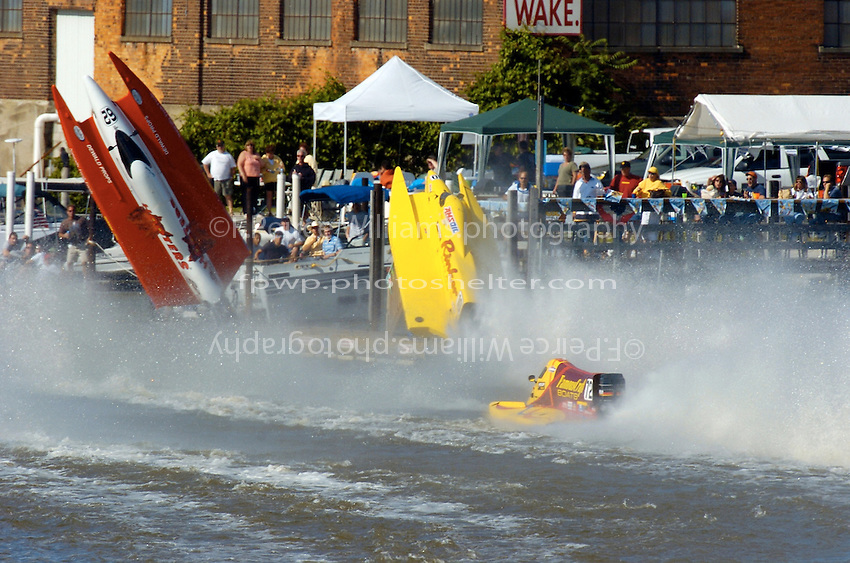 2004 Bay City River Roar, Bay City, Michigan, 26-27 June, 2004..Frame 2:.Chris Fairchild (L, #62) and Terry Rinker (R,#10) come together during the inverted start for Saturday's 2 heat race. Both boats suffer a blowover, Fairchild's boat landing upside down in the river only to be run over by Todd Bowden. During Rinkers crash, his boat snagged a pier with the lower unit, ripping it away. The boat continued skyward, hitting the staircase from the lower to the upper pier and then striking a piling with the right rear of the hull, with that large chunk falling to the pier below (to be seen in a later picture. Rinker continued his backflip, finally landing just a few feet from a docked pleasure boat filled with spectators. No one was injured in the accident and both drivers made the restart in their backup boats...©F. Peirce Williams 2004..F. Peirce Williams .photography.P.O. Box 455 Eaton, Ohio 45320 USA.p: 317.358.7326 e: fpwp@mac.com