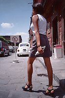 A tall mexican woman cross the street in San Miguel de Allende.  Mexico