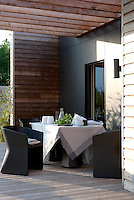 An outdoor dining area is situated in the lee of a projecting wall on the terrace