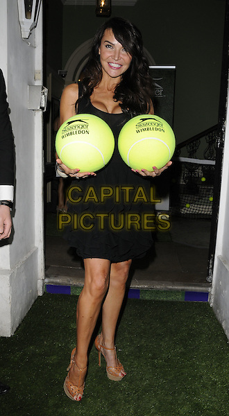 Lizzie Cundy .At the Slazenger Party, The House of St. Barnabas, Greek Street, London, England, UK, 23rd June 2011..full length black sleeveless dress funny oversized tennis balls boobs breasts holding .CAP/CAN.©Can Nguyen/Capital Pictures.