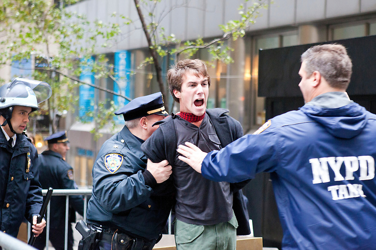 """A man is arrested as hundreds of protesters march with the aim to shut down Wall Street and the Stock Exchange on November 17, 2011 in New York City.  The action was part of a day of protests celebrating the two month anniversary of the """"Occupy Wall Street"""" movement.  While many workers were inconvenienced by the human (and police) barricades, the Stock Exchange opened on schedule."""
