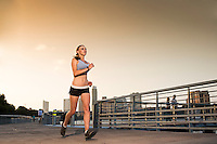 Woman runner training for marathon on The Boardwalk Trail along Lady Bird Lake, Austin Skyline background.
