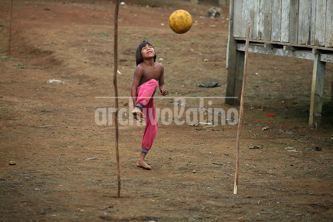 An  Emberá Dóvida  indigenous kid   plays soccerin Choco department, in the Pacific coast of Colombia