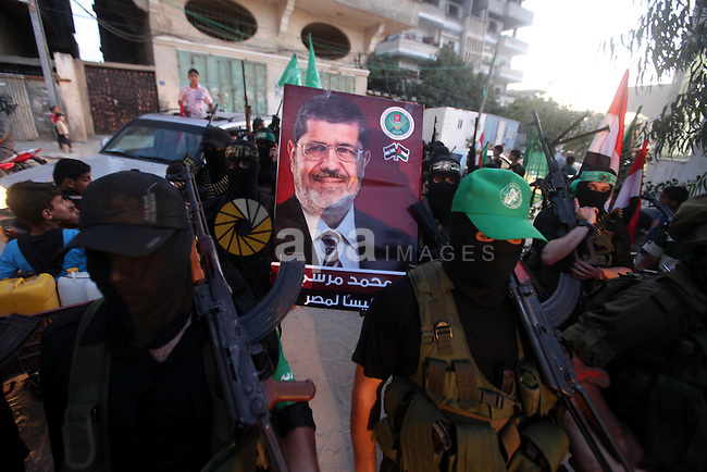 Hamas militants hold a poster depicting Mohamed Morsy of the Muslim Brotherhood after the Egyptian Presidential election committee announced him as victor. The Muslim Brotherhood's Mohammed Morsi became Egypt's first freely elected president, the election commission said, sparking mass celebrations in Cairo where tens of thousands of his supporters had gathered. Morsi, an engineering professor, won 51.73 per cent of votes in the June 16-17 presidential run-off, commission head Farouk Sultan said. Photo by Majdi Fathi