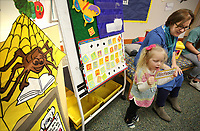 NWA Democrat-Gazette/DAVID GOTTSCHALK Irene Gibson, 5, assists Erin Renollet, children's librarian, with the days of the week Wednesday, February 28, 2018 during the Rattle & Rhyme Toddler Time event that the Springdale Public Library. The theme on Wednesday was bugs and the children listen and sang bug themed songs, listened to bug themed books and made a lady bug craft.