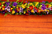 A beautiful purple, yellow and red haku lei (Hawaiian floral headpiece) on a koa background.