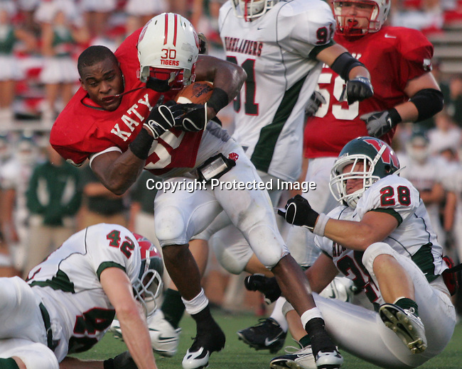 Katy's running back Aundre Dean loses his helmet as he spins for extra yardage against the Woodlands.   The Katy Tigers played the Woodlands Highlanders at Rhodes Stadium in Katy, Texas September 8, 2007. (Freelance/Margaret Bowles)