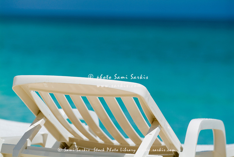 Empty white deck chair on a beach with bright blue waters, Cayo Santa-Maria, Cuba.