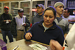 Denise Sandoval sees the tangible results of another week's work at the Excel Corporation pork processing plant as Stoplight Liquors owner Lisa Mincy cashes her paycheck. Immigrants, mostly Mexican, have flocked to formerly all-white Beardstown for Excels plentiful jobs and relatively high wages, $10.70 to $11.95 an hour.