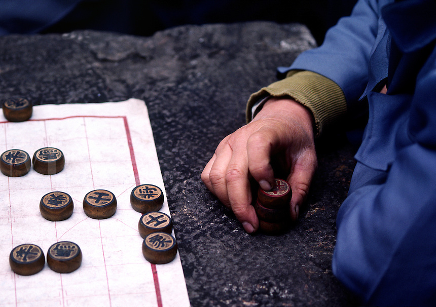 A Chinese MAN CONCENTRATES as he plays a game of CHINESE CHECKERS in KUNMING - YUNNAN, CHINA.