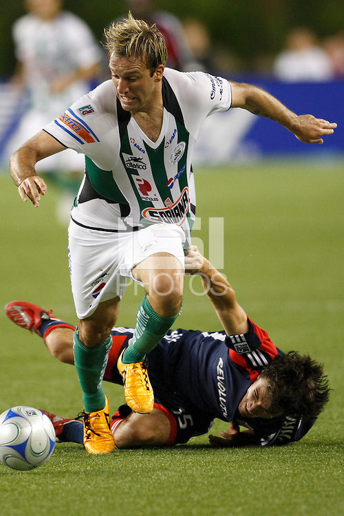 Santos Laguna forward Vicente Matias Vuoso (30) is pulled down by New England Revolution defender Michael Parkhurst (15). The New England Revolution defeated Santos Laguna 1-0 during a Group B match of the 2008 North American SuperLiga at Gillette Stadium in Foxborough, Massachusetts, on July 13, 2008.
