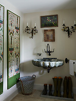 In the bathroom, a marble wall-mounted washbasin, wrought-iron scones and stone floor gives the room a rustic feel.