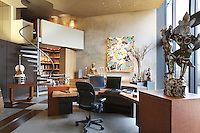 Designer Ron Mann refurbished a modern penthouse in London overlooking the Thames. Mann designed the staircase and the desk in the studio. Robert Rauschenberg's Tibetan Garden Song, 1986, is at left. A lithograph by Frank Stella hangs on the rear wall.  Interesting pieces of Asian art are strategically placed around the room.