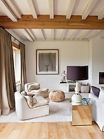 One end of the open plan living area is furnished with a pair of comfortable, cream leather chairs