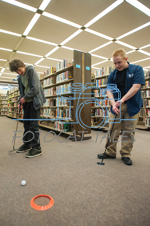 Ryan Fitzsimmons attempts a putt while Carson City Library Assistant Aubrey White watches during the Mini Golf Night at the Carson City Library on Friday May 9, 2014. Kids and parents built a custom mini golf course throughout the library using anything at their disposal and engineering ideas to make a difficult course. Everything from tables to shelves were used to create creative courses.<br />