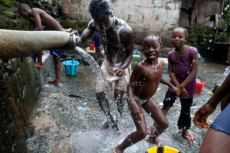 Young people bathe at a sawmill drainage pipe in Mabella quarter, Freetown, Sierra Leone, Aug. 13, 2012. Médecins Sans Frontières Belgium, in collaboration with the Sierra Leone Ministry of Health, is running four emergency cholera treatment centers to keep up with the number of patients. Many of the roughly 120 daily patients seen by the MSF team come from extremely impoverished areas of the densely-populated capital, where proper systems for drainage and waste disposal are almost non-existent. Outbreaks of water-borne diseases like cholera become even more likely during the rainy season, which is expected to last at least two more months.