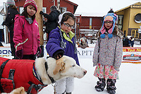 Youngsters Beth Booshu (L) and Kelsi James of Nome pet Jason Mackey dogs in the finish chute at Nome on Thursday March 13 during the 2014 Iditarod Sled Dog Race.<br /> <br /> <br /> PHOTO (c) BY JEFF SCHULTZ/IditarodPhotos.com -- REPRODUCTION PROHIBITED WITHOUT PERMISSION