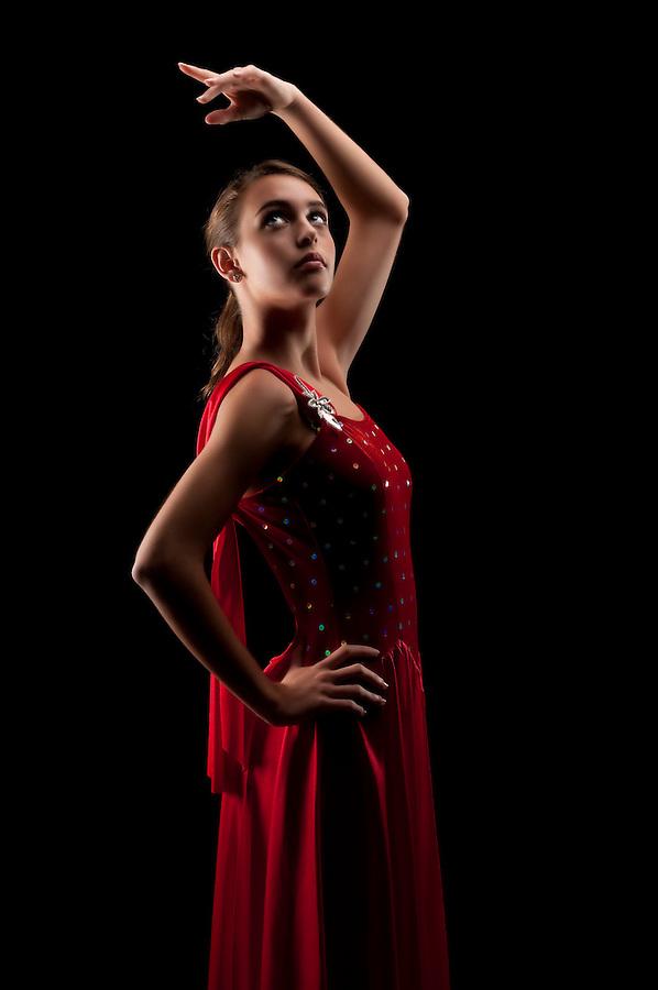 Young caucasian ballerina posing in dim light. Low key image.