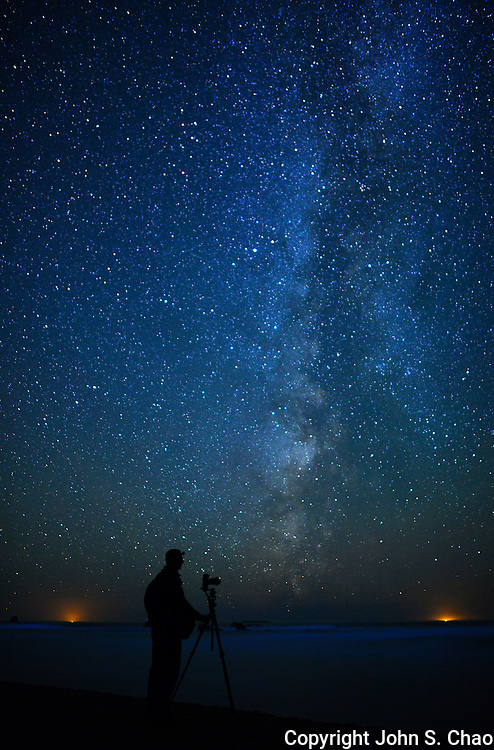 Milky Way passes by silhouetted photographer at Ruby Beach, Olympic National Park, Washington State. 2 lights on horizon are fishing boats.