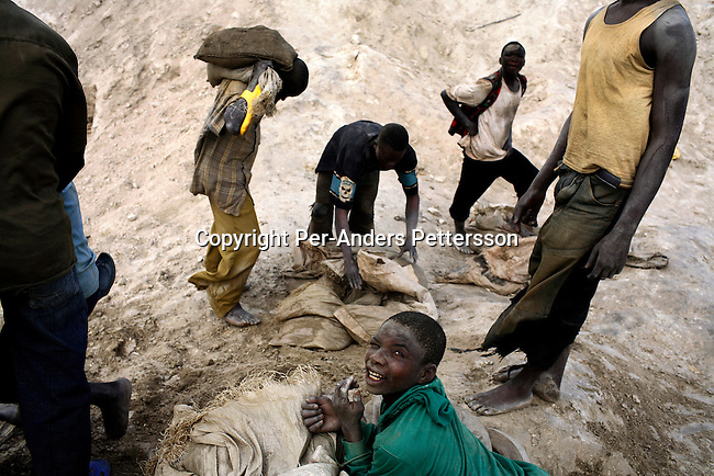 LUBUMBASHI, DEMOCRATIC REPUBLIC OF CONGO - DECEMBER 13: Unidentified young boys carry bags of copper on December 13, 2005 in Ruashi mine about 20 kilometers outside Lubumbashi, Congo, DRC. About 4,000 artisan miners and children as young as eight years old work in the mine under dangerous conditions. Every month a few of the miners are killed. Congo has one of the largest Copper deposits in the world and most of it is exported to China. It?s fueling the thirst for minerals for China?s economic boom. The young men who works in the mine makes a few US dollars a day, and the children much less. The mine is about one hundred years old and has been a source of wealth for the Katanga province for many years. In recent years many foreign companies and shady business people has moved into Congo to plunder its wealth. The country has no elected government and the corruption is rife. Border and customs officials are easily bribed. Congo has had a civil war since 1997 and it?s estimated that nearly 4 million people has died in fighting and because of lack of health care. .(Photo: Per-Anders Pettersson/Getty Images).
