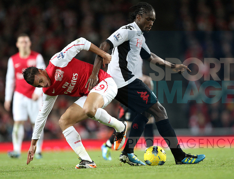 Arsenals Marouane Chamakh tussles with Fulhams Dickson Etuhu