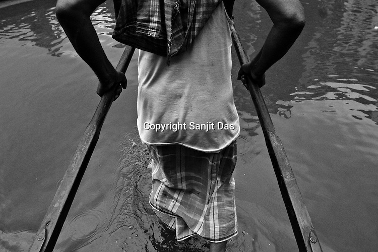 A rickshaw puller takes his customer through the water logged streets on his rickshaw in Calcutta, India. 93 out of every 100 rickshaw pullers are homeless. They sleep after the city sleeps and wake up before everyone else does. Many of them are the sole bread earners for their family. Many plus 40. Many minus any other specialisation for any other job. Of the twenty four thousand rickshaw pullers, only 387 have licenses. .Many rickshaw pullers earn a meagre wage of 100-150 rupees (US $ 2.25-3.5) a day of which they have to give a daily rickshaw rent of 60 (US$ 1.35) rupees to the agent at the end of the day.