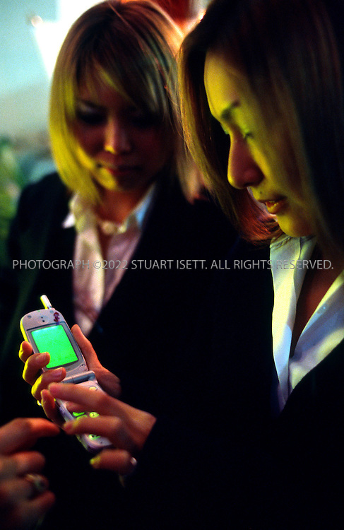 3/15/2002--Tokyo, Japan..Two Japanese high school girls using their mobile phones to send email...All photographs ©2003 Stuart Isett.All rights reserved.This image may not be reproduced without expressed written permission from Stuart Isett.