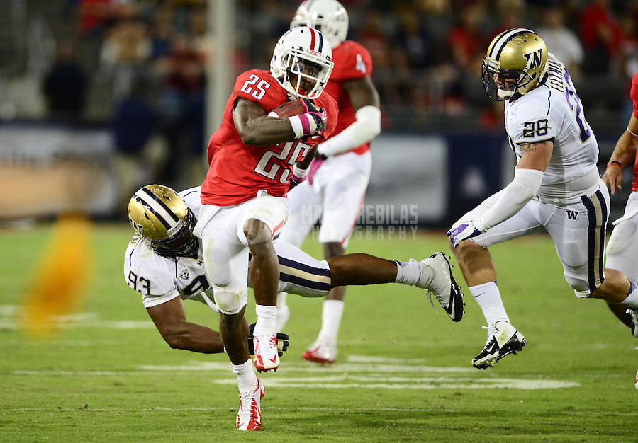 Oct. 20, 2012; Tempe, AZ, USA; Arizona Wildcats running back (25) Ka'Deem Carey runs the ball in the second half as he is tackled by Washington Huskies defensive end (93) Andrew Hudson at Arizona Stadium. Arizona defeated Washington 52-17. Mandatory Credit: Mark J. Rebilas-