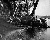 Landing operations on Redova Island, Solomon Islands, 30 June 1943.  Attacking at the break of day in a heavy rainstorm, the first Americans ashore huddle behind tree trunks and any other cover they can find.  (Navy)<br /> NARA FILE #:  080-G-52573<br /> WAR &amp; CONFLICT BOOK #:  1176