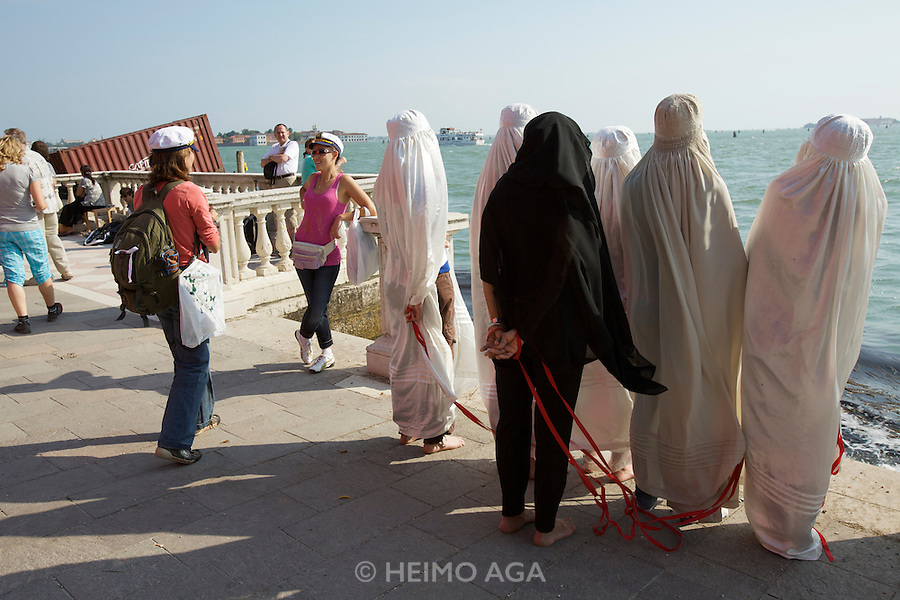 Pakistani artist Maimuna Feroze Nana (in black) with her performance about female conditions in muslim countries, with the help of Western women wearing the burka, in front of the Giardini.