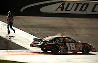 Feb 21, 2009; Fontana, CA, USA; NASCAR Nationwide Series driver Kyle Busch runs to get the checkered flag after winning the Stater Brothers 300 at Auto Club Speedway. Mandatory Credit: Mark J. Rebilas-