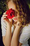 Teenage female holding a red rose to her face looking down