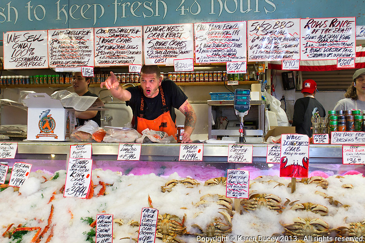 An employee manning the counter at the Pike Place Fish Market speaks to a customer in Seattle, Wash., on July 1, 2013. (photo © karenducey.com)