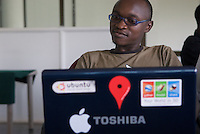 "A software engineer at John Gosiers' startup ""Appfrica"". A recent graduate of Makerere Universitites' Computer Science department, is a convert to Open Source Software. Western software tools such a Microsoft servers are disproportionaly expensive compared with people and hardware costs in Africa. The price of bandwidth, more expensive than in developed markets also puts Ugandan's at a disadvantage: ""We have to use Google like everyone else, to read documentation, to write code"". Ambition is one thing not lacking: ""We're going to be like India in 10 years. We're going to get those contracts""."