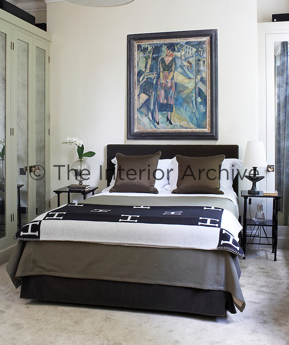 A framed painting above the double bed adds a touch of colour to this contemporary bedroom