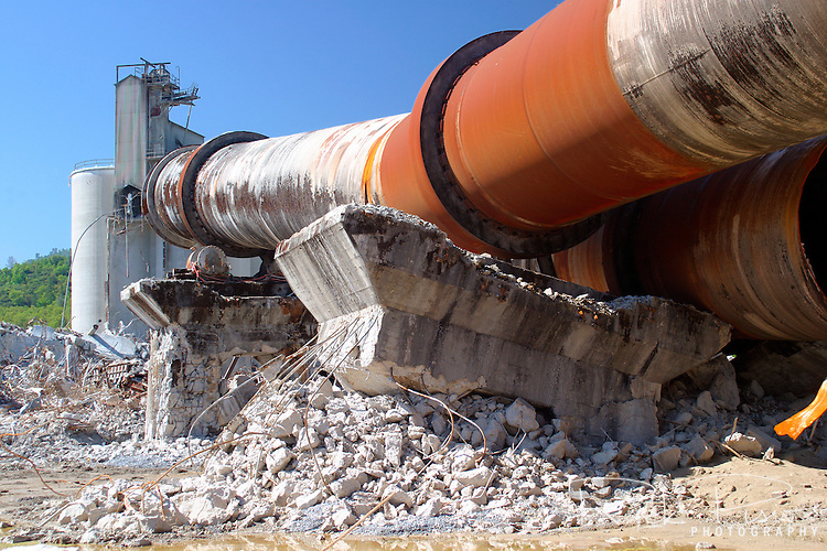The partially demolished concrete kiln and support structure wait to be hauled away from the Calaveras Concrete site near San Andreas, California. Built on speculation of a California building boom mining engineer William Wallace Mein raised 2 million dollars from investors and incorporated Calaveras Cement in San Andreas. In 1926 the plant was built and supplied 750,000 barrels of cement for the Pardee Dam in that same decade. In 1936 the plant contributed 400,000 barrels of special formula cement for the Oakland-San Francisco Bay Bridge. In the 1980's the plant was closed and sat idle until 2005 when it was demolished. Photographed 04/05.